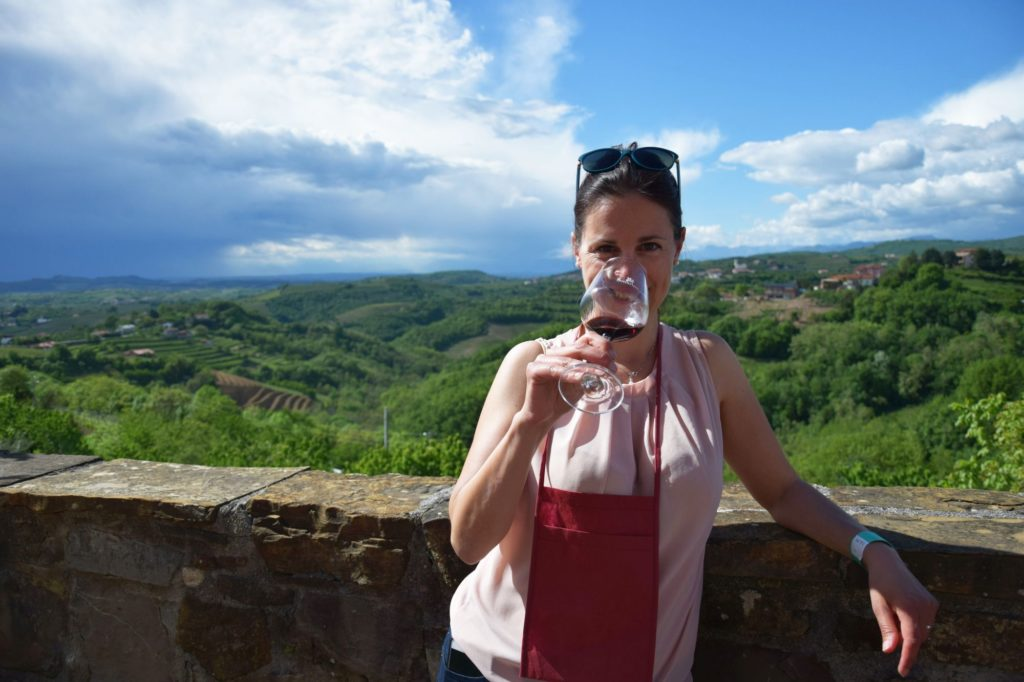 Food and wine blogger drinks wine from wine glass with views of Goriška Brda