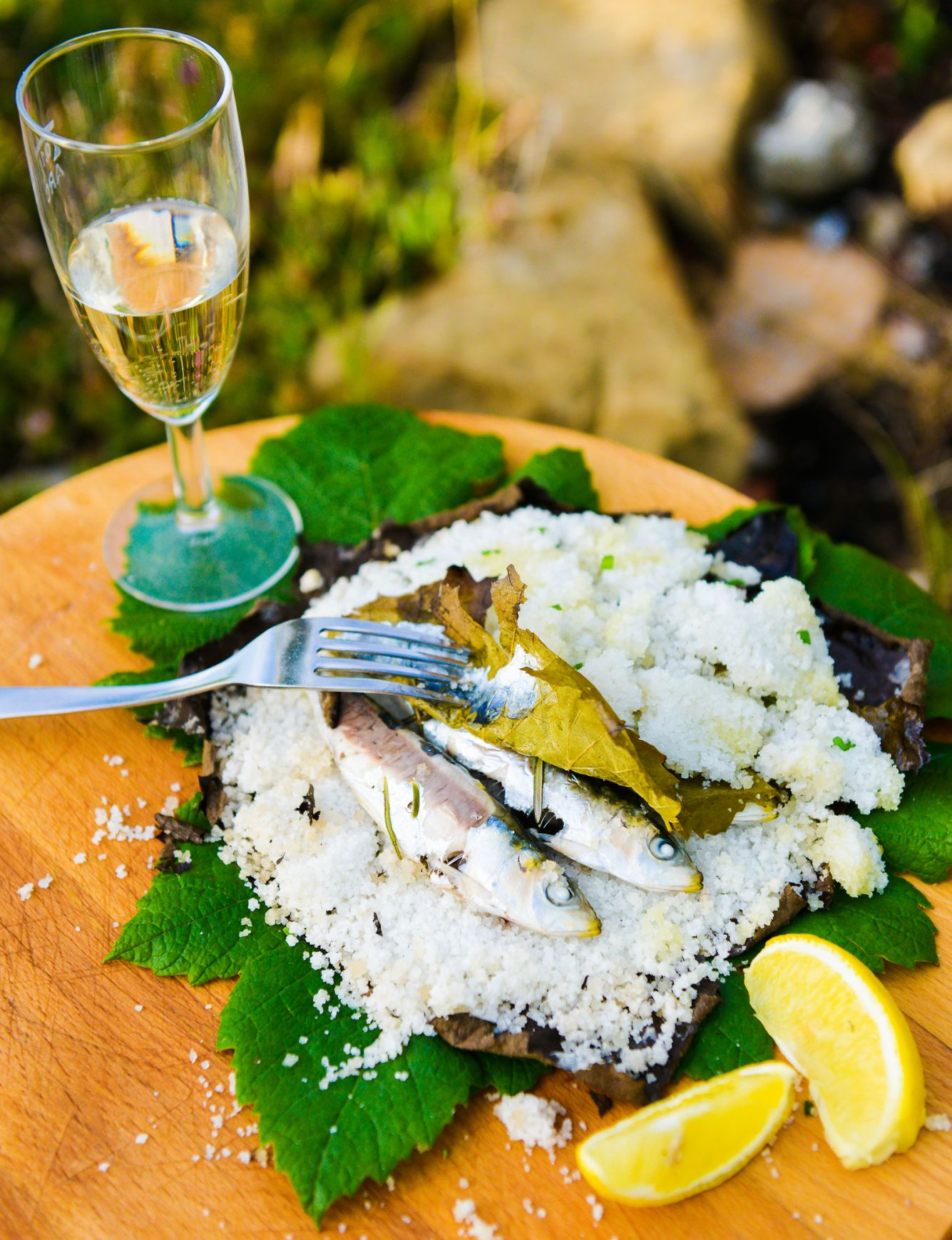 Food presentation of fish served with lemon and a glass of white sparkling wine
