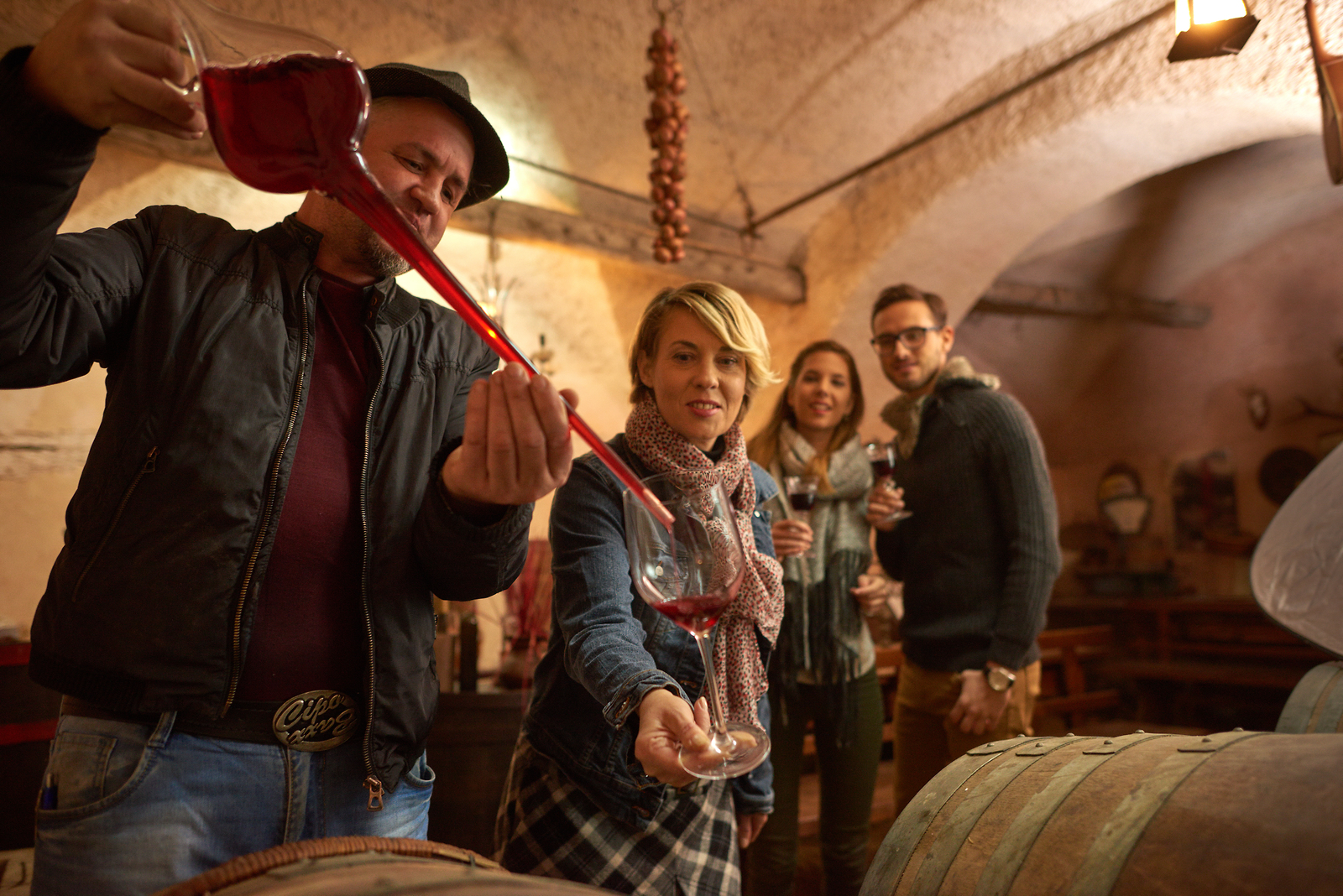 A Slovenian winemaker pours young red wine into a wine taster's glass
