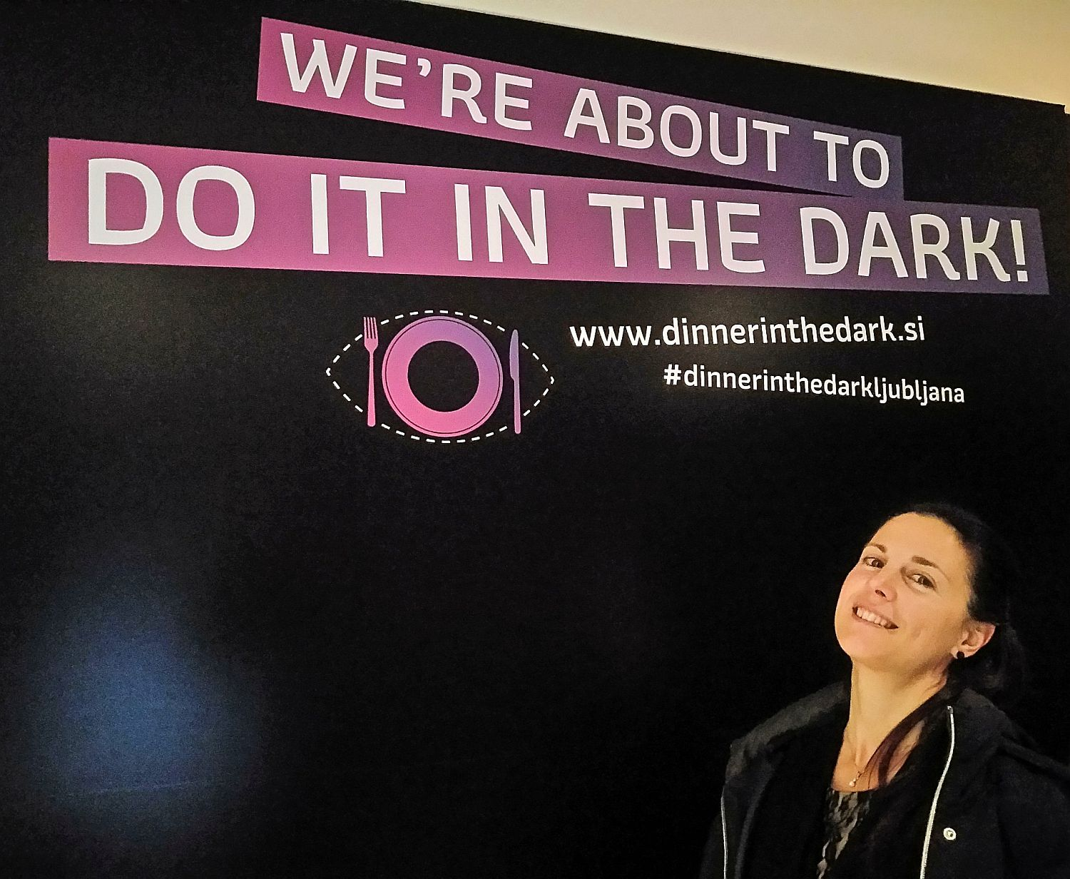Denise Rejec, Wine Dine Slovenia blogger, poses in front of Dinner in the Dark photo background