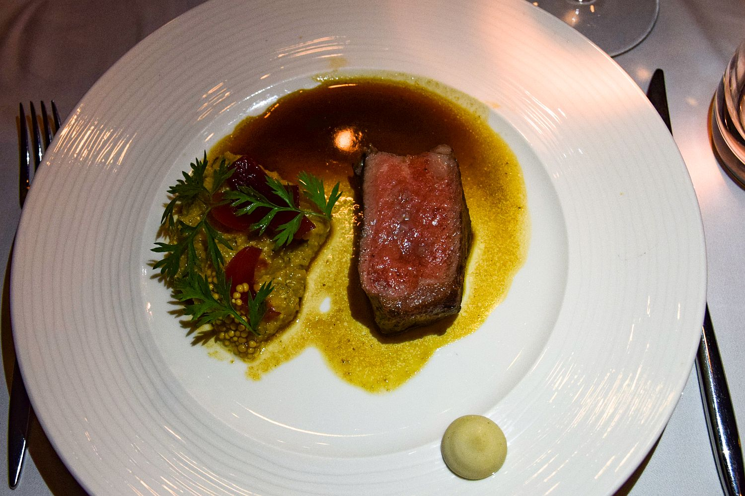 Dry-aged tenderloin with bone marrow sauce, mushroom polenta, anchovy mayonnaise, and pickled mustard seeds by Strelec Restaurant chef Igor Jagodic