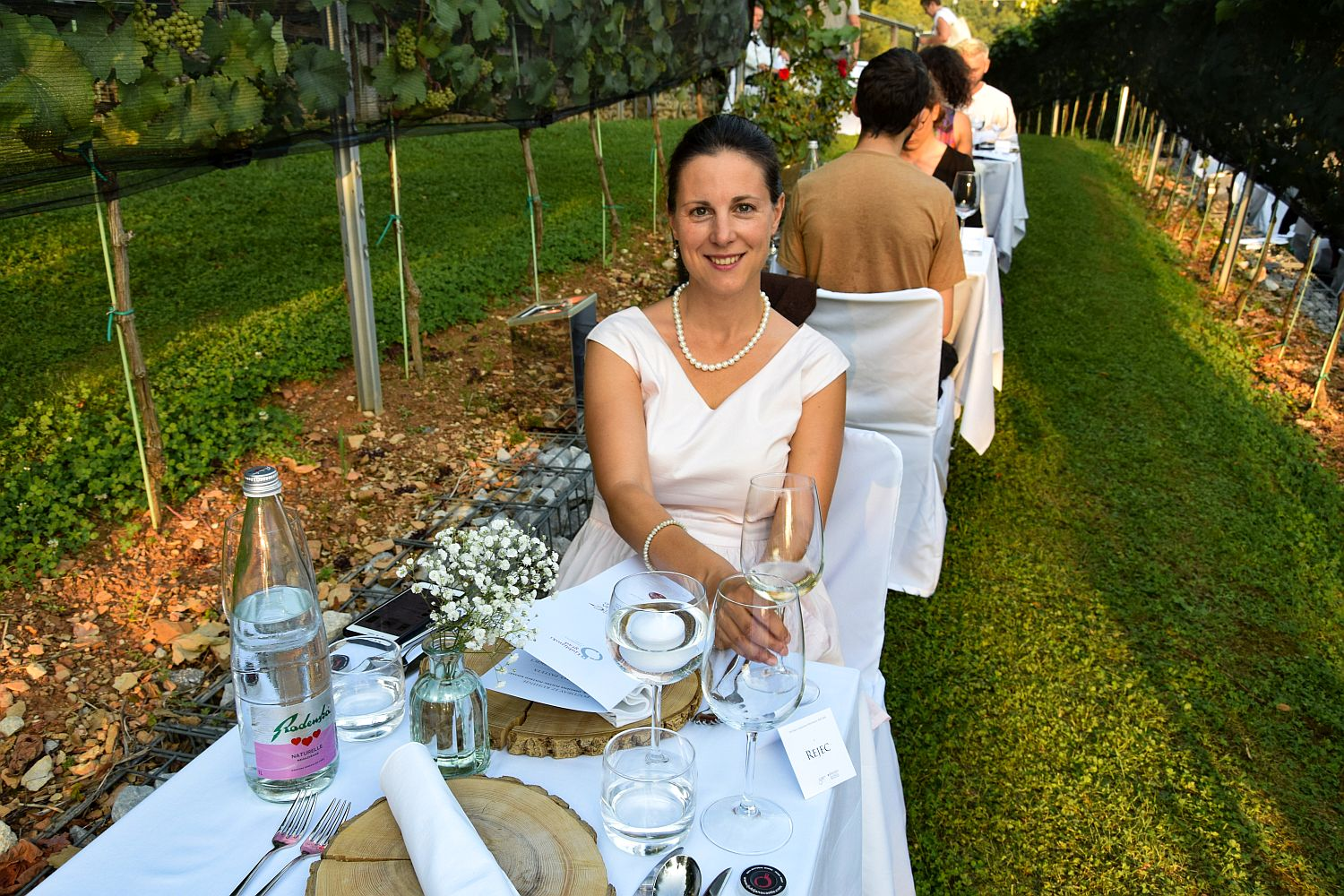 Food blogger Denise Rejec of Wine Dine Slovenia sits at a dinner table during the Strelec Restaurant Ljubljana Castle Vineyard dinner