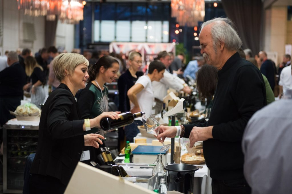 Winemaker pours glass of wine at Slovenian wine festival