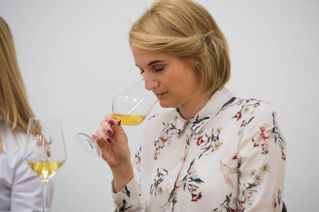 Slovenian wine queen smells white wine in wine glass at Slovenian wine festival