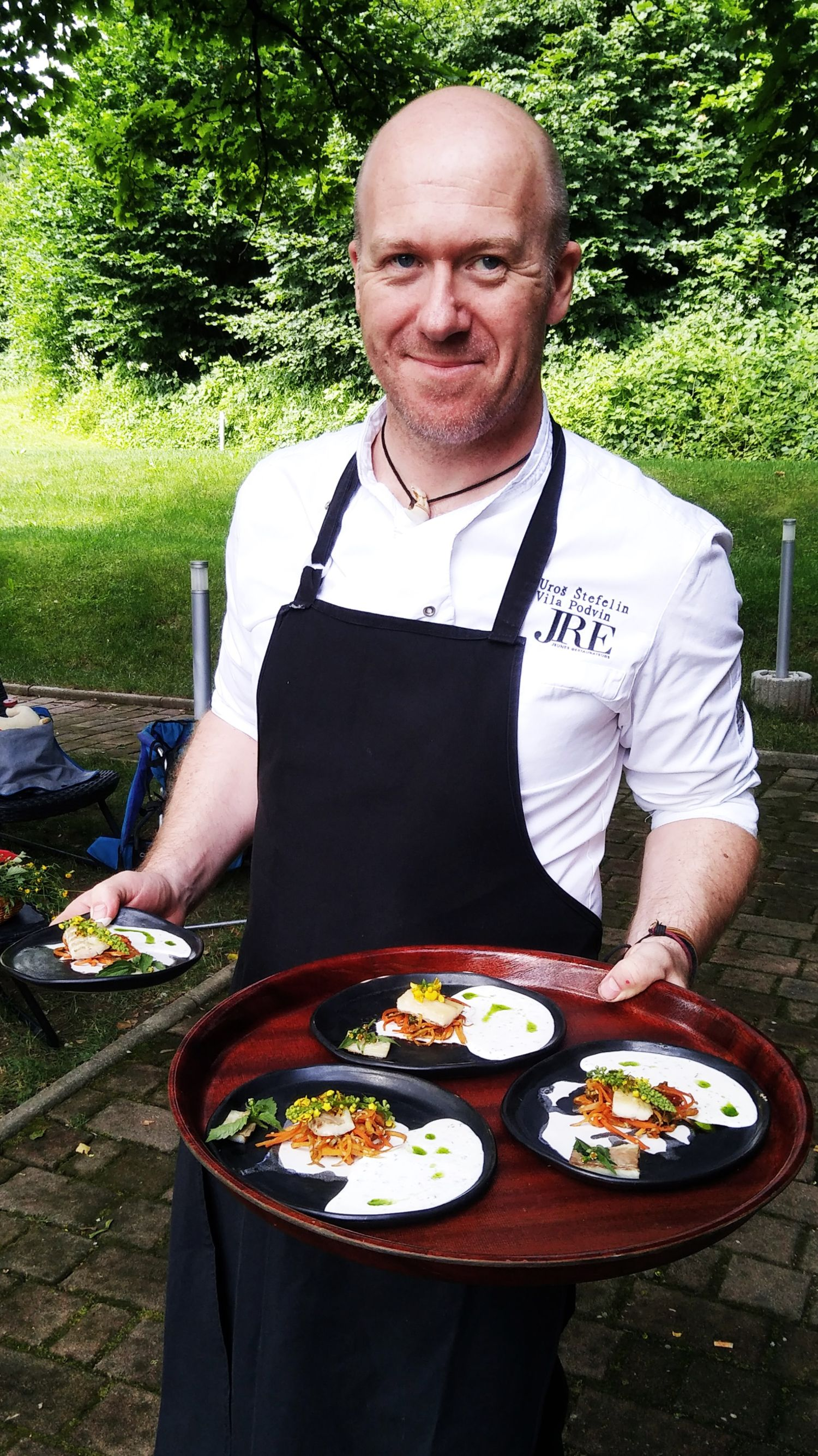 Chef Uroš Štefelin of Vila Podvina restaurant with four plates of smoked sea bass Fonda fillet, accompanied by yogurt sauce with dill oil and cabbage thistle, and marinated vegetables