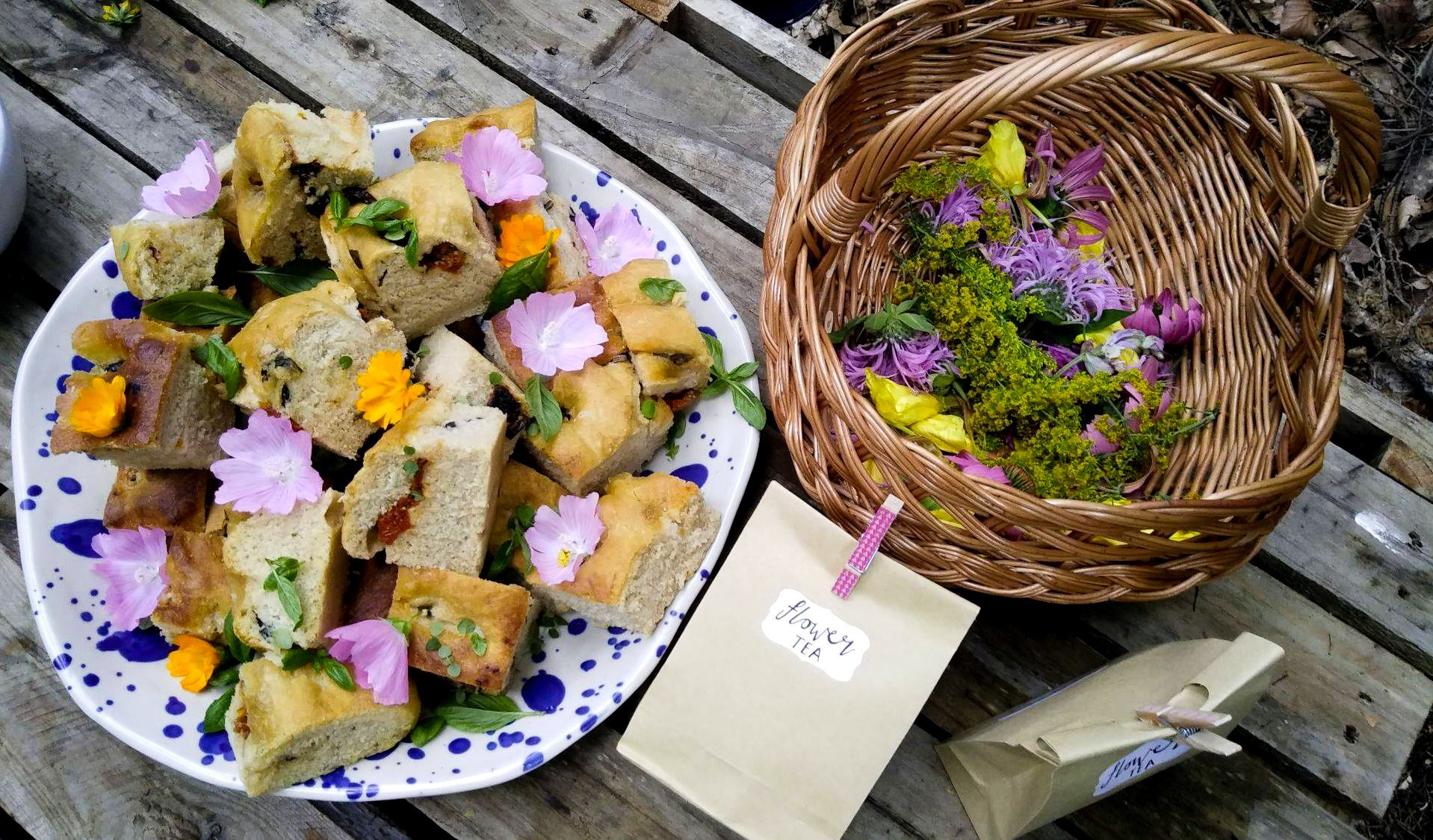 Dish of olive and sun-dried tomato focaccia, a basket of edible flowers, and two bags of flower tea