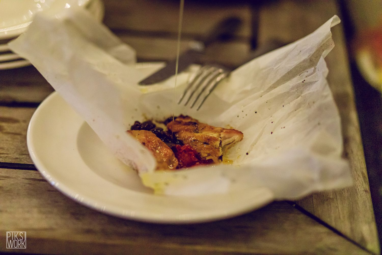 Chicken cooked 'al cartoccio' in a baking paper pouch together with cherry tomatoes and olives