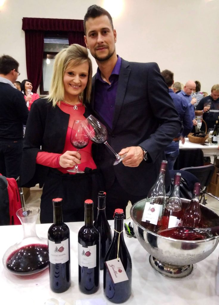 Winemakers pose with bottles of wine