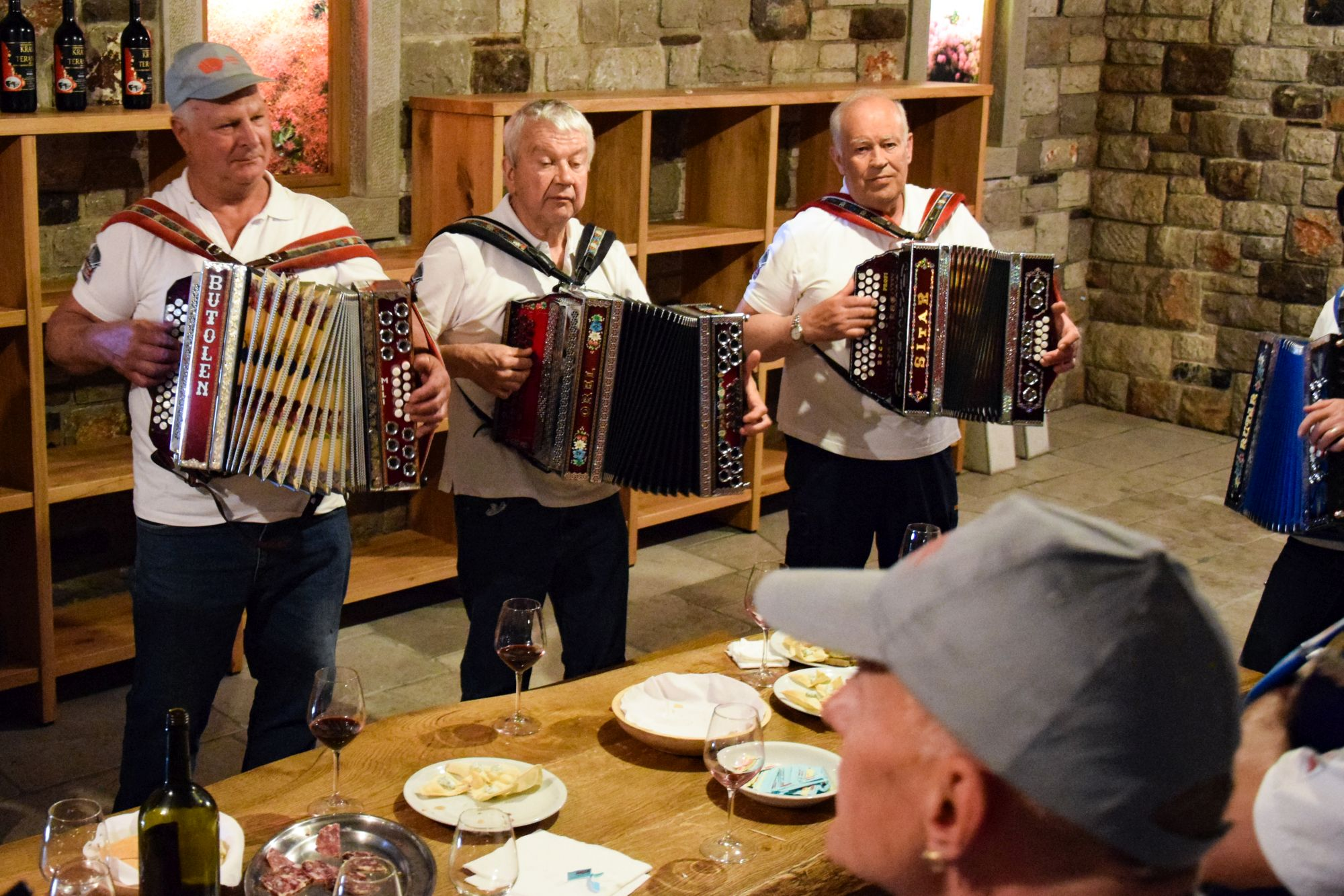 Accordion players entertain during a wine tasting session in a Karst wine cellar
