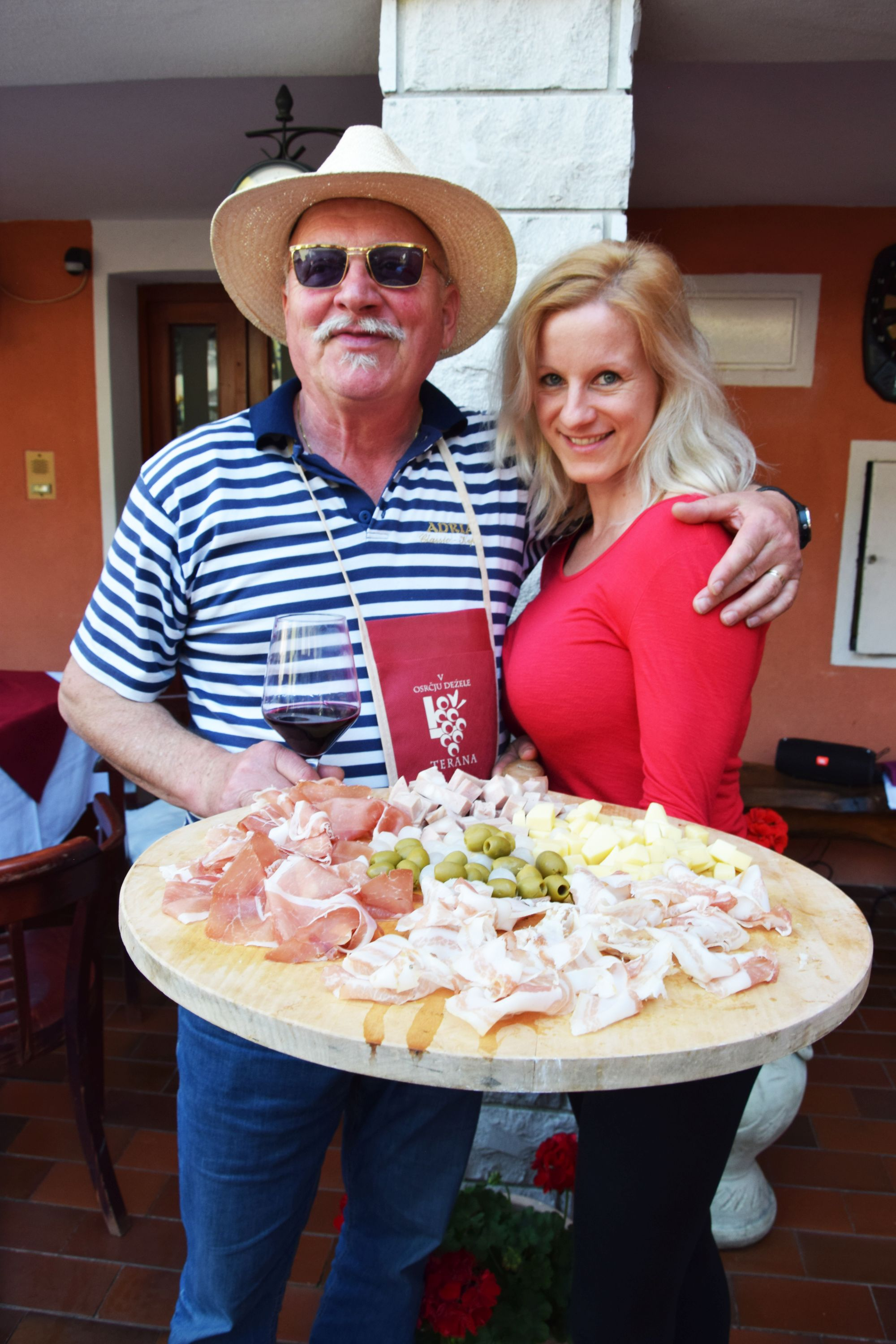 Man and woman pose with cured meats and cheese platter