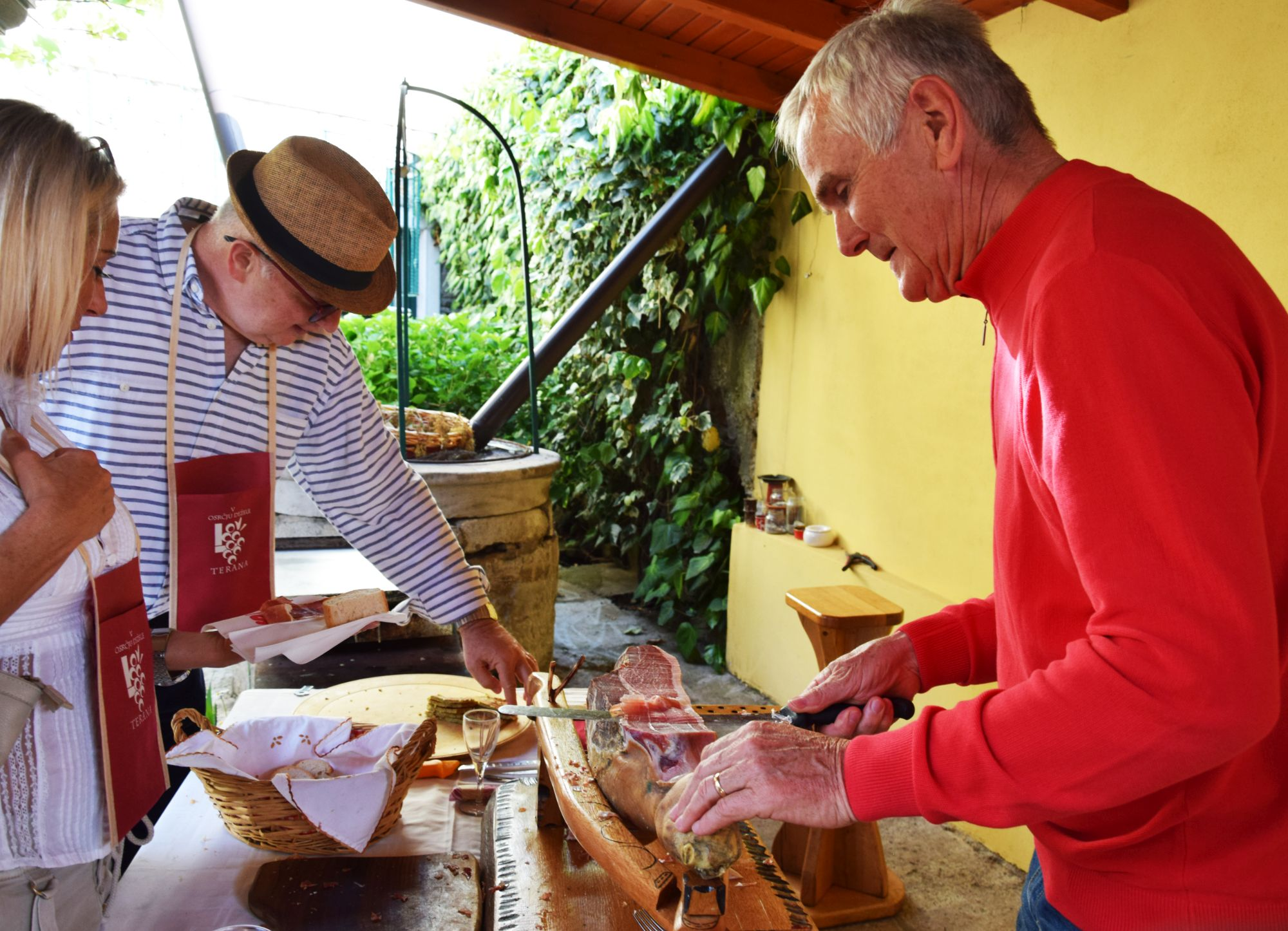 Man cutting slices of prosciutto from a pig leg