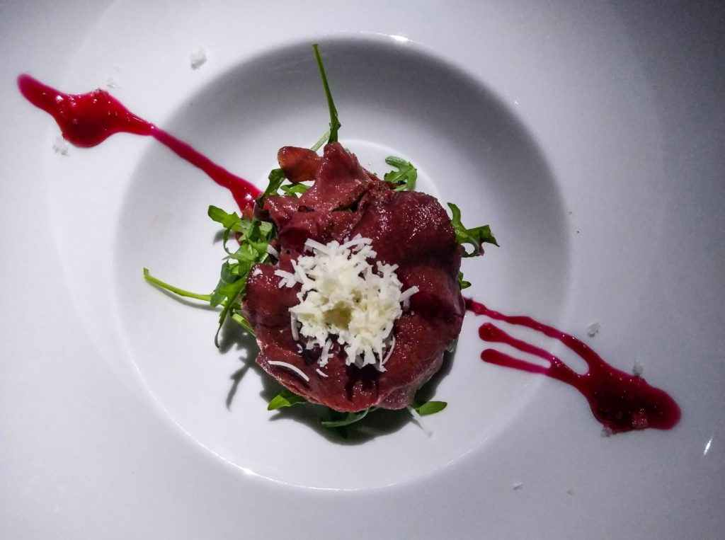 Orange marinated deer carpaccio drizzled with a balsamic plum cream