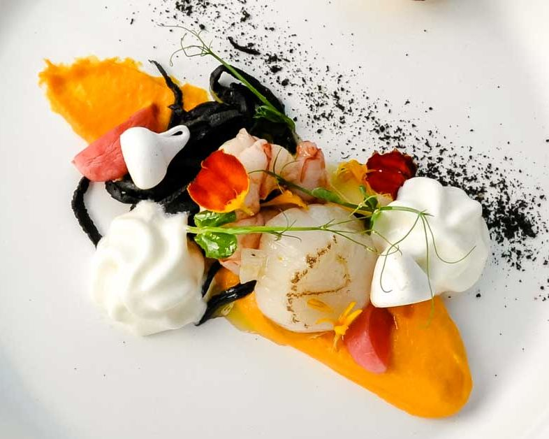 Roasted scallop with black noodles on carrot cream with marinated royal shrimp, squeezed radishes, ginger foam, rice chips and dried white pepper