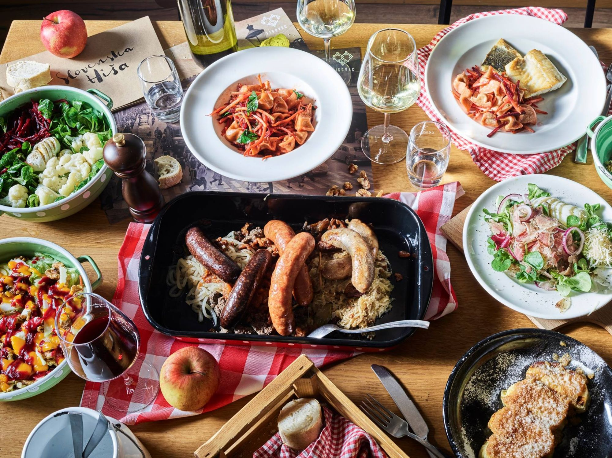 Table with various food dishes and glasses filled with wine