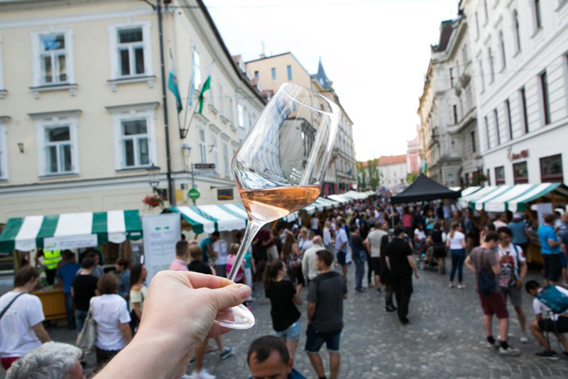 Hand holding a glass of wine against background of Ljubljana buildings and wine festival