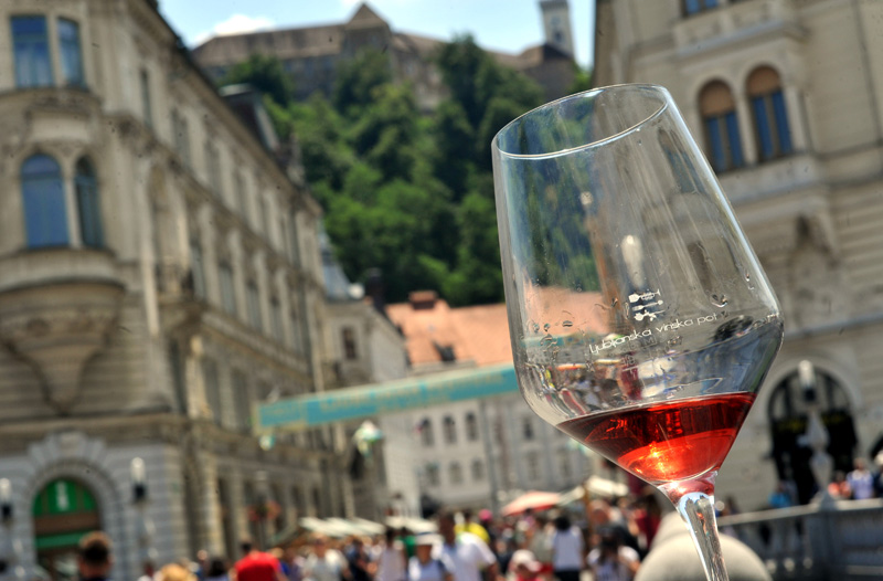 Wine glass with rose wine with Ljubljana building in background