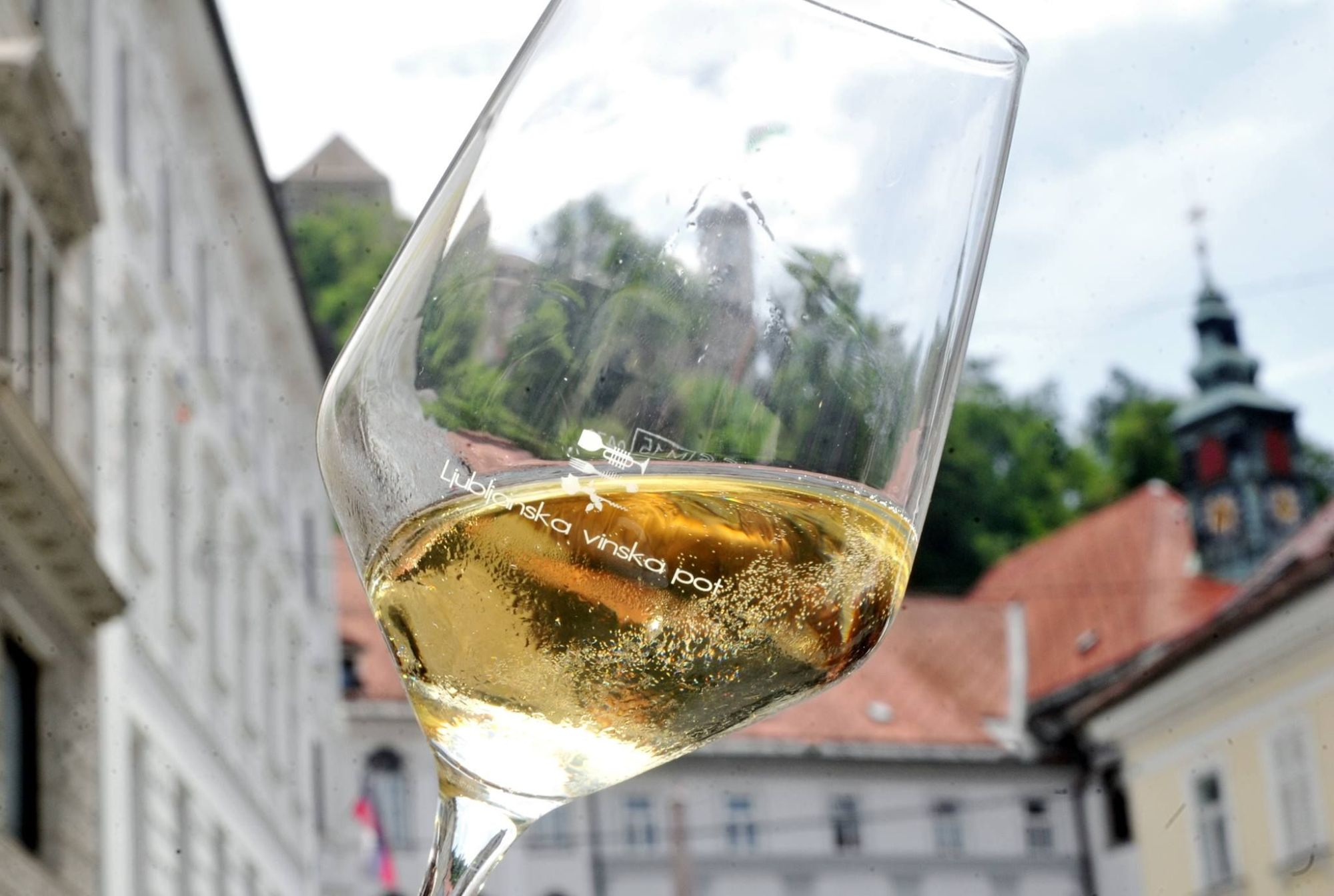 Wine glass with white wine with Ljubljana building in background at the Ljubljana Wine Route