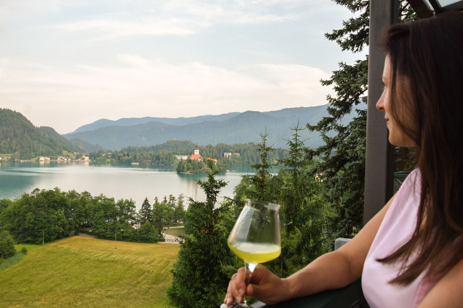 Denise Rejec of Wine Dine Slovenia ejoying the view of Bled Island at a food and gin pairing at Restaurant 1906 Bled